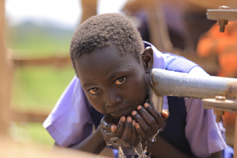 African Borehole Projects: Child drinking fresh water